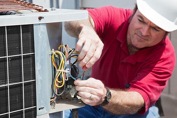 hvac technician rewiring a compression unit | Cargo Van Accessories for HVAC Techs | Adrian Steel
