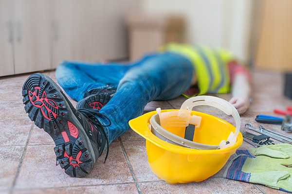 injured worker laying on the ground with construction equipment | Prevent injury on the job | Adrian Steel