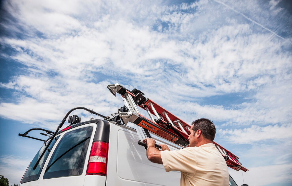 Man removing ladder from the top of van